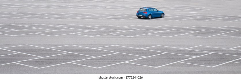 Blue car in an empty parking lot. Horizontal banner with copy space. Automobile without brand.
