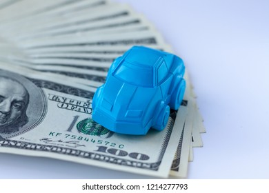 A blue car figure stands on a table covered with hundred dollars bills. Concept for advertising loan, collateral, pawnshop, car rental. Money cars concept or idea.