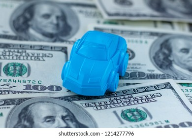 A blue car figure stands on a table covered with 100 dollars bills. Concept for advertising loan, collateral, pawnshop, car rental. Money and cars.