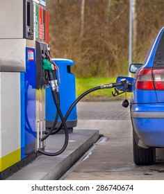 Blue car filling up with fuel at the gas station against inflated prices