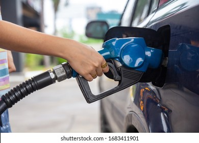 Blue car at gas station filled with fuel. Closeup woman hand pumping gasoline fuel in car at gas station.woman refuel car petrol pump filling gas at gas pump.