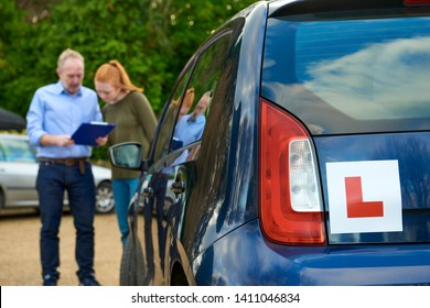 Blue car with a learner driver sign with driving student and instructor in the background