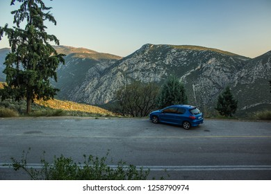 blue car on stay on landmark country side road beautiful mountain ridge background environment