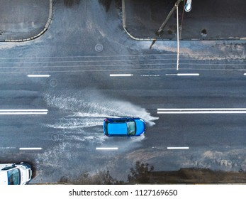 blue car on wet street after heavy rain. splashes and puddles on flooded road. aerial view
