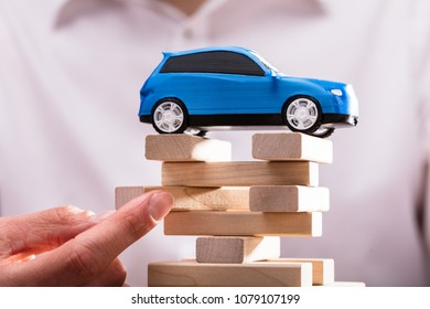 Blue Car Over Businessperson's Finger Arranging Wooden Blocks.