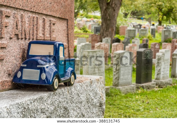 Blue car toy on a tombstone in a Montreal cemetery (Famille means Family in french)