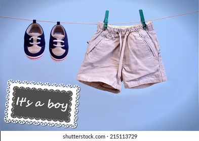A blue card hanging on line with baby booties and shorts isolated on a blue background for you message, It is a Boy Announcement