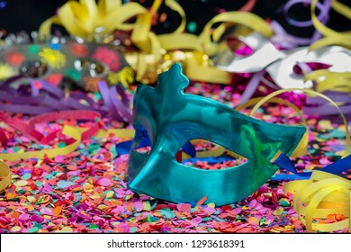 blue carnival mask over confetti and multicolored streamers on black background