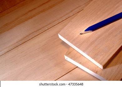 Blue carpenter pencil on red oak wood boards in a carpentry workshop for furniture making