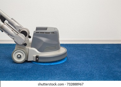 Blue carpet chemical cleaning with professionally disk machine. Early spring regular clean up. Cleaning service concept.