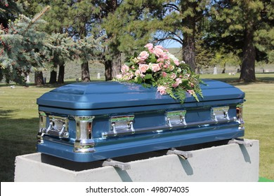 A blue casket at a small cemetery with beautiful flowers set on top. A final resting place.