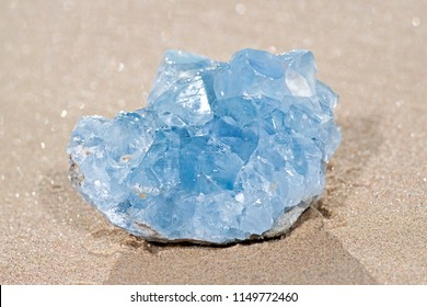Blue Celestite cluster from Madagascar on wet sand on the beach at sunrise.