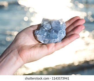 Blue Celestite cluster from Madagascar in woman's hand at sunrise in front of  the lake.