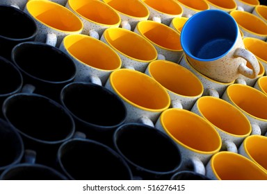 Blue Ceramic Mug On Top of Yellow and Black Ceramic mugs in repetition