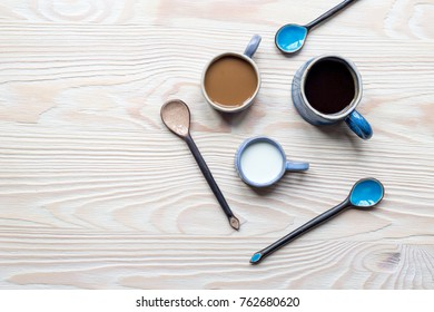 Blue ceramic spoons and cups of black coffee and coffee with milk on white background flat lay mock up.