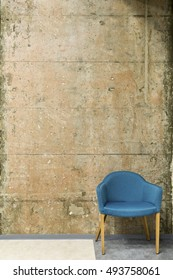 Blue chair in front of a concrete wall with copy space