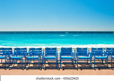 Blue chairs on the Promenade des Anglais in Nice, France. Beautiful turquoise sea and beach