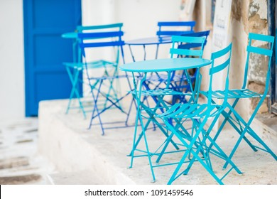 Blue chairs and table on street of typical greek traditional village with white houses on Mykonos Island, Greece, Europe