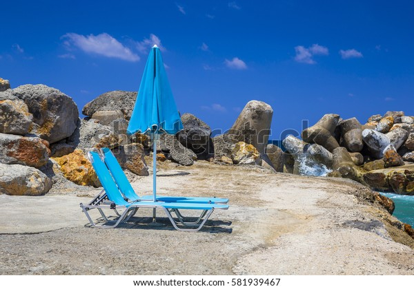 Blue chairs and umbrella on a beach of Crete, Greece