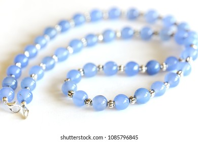 Blue Chalcedony beads necklace with silver spacer isolated on white background