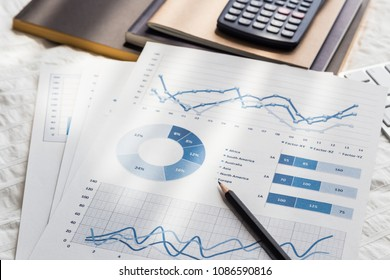 Blue chart graph data analysis documents, pencil, calculator, notebooks on wrinkle white duvet bedding fabric. Morning daylight in bedroom. Freelance job work at home, business, education concepts.