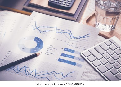 Blue chart graph data analysis documents, pencil, modern keybord, glass of water, calculator, notebooks on bed. Morning daylight in bedroom, vintage retro style. Freelance job work at home concept.