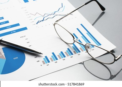 Blue charts, glasses and pen. Financial report on gray reflection background.