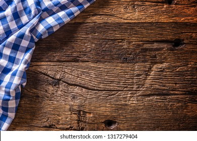 Blue checkered kitchen tablecloth on rustic wooden table.