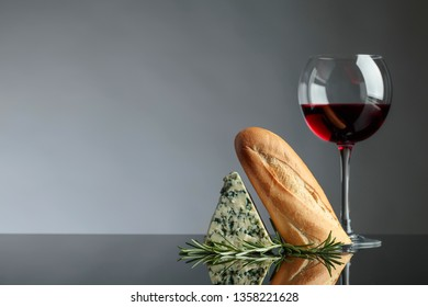 Blue cheese with bread, rosemary and red wine on a black reflective background. Copy space for your text.