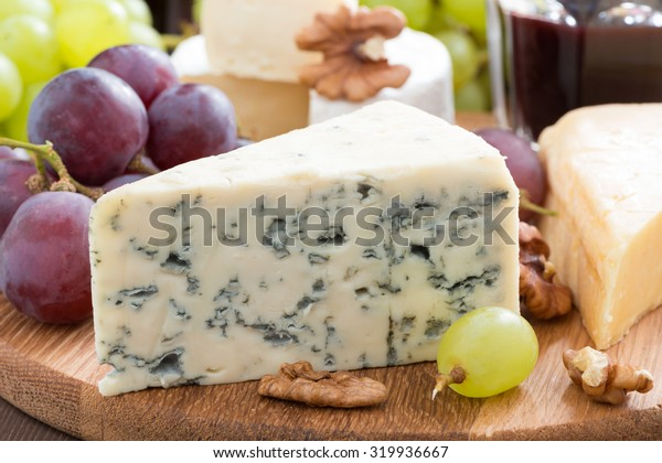 blue cheese, cheddar, camembert and fresh grapes, close-up