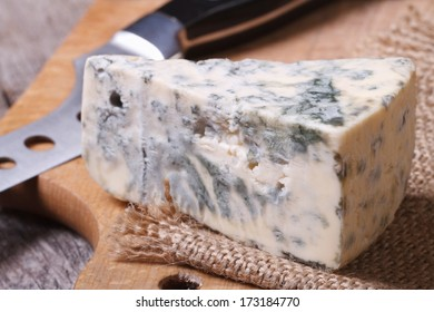 Blue cheese close-up on a kitchen wooden board and knife
