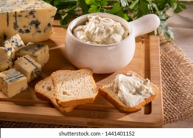 Blue cheese cream and toasted bread on wood background. Pate de gorgonzola in Brazil.