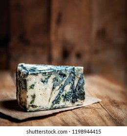 Blue cheese Gorgonzola on a rustic wooden background. Mold cheese with copyspace and dark backdrop