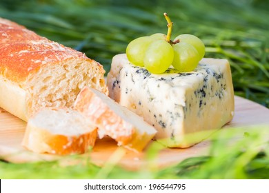 Blue cheese with grapes and baguette on wooden plate outdoors. Shallow DOF