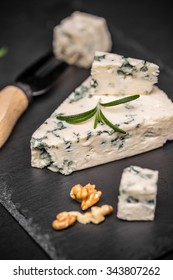 Blue cheese with nuts on black slate