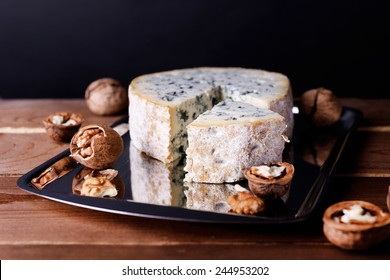 Blue cheese with nuts on metal tray and wooden table and dark background