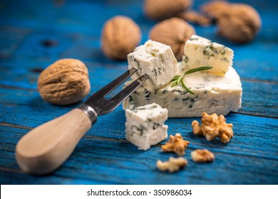 Blue cheese with nuts on blue wooden table