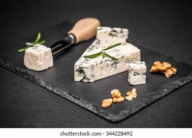 Blue cheese on black slate background