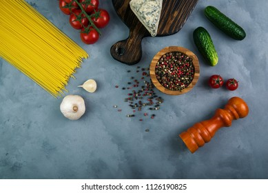 Blue cheese on wooden cutting near the peppermint, vegetables and noodles on concrete background