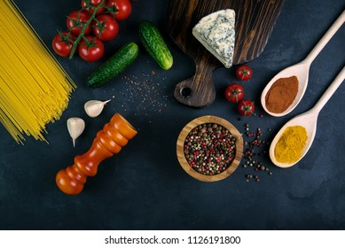 Blue cheese on wooden cutting near the peppermint,vegetables, salad and noodles on concrete background