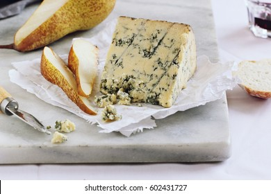 Blue cheese and pear on a marble cutting board. Old english Stilton cheese.