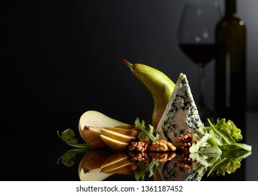 Blue cheese with walnuts, pear and greens on a black background. In the background, the silhouette of a glass of red wine. Copy space.