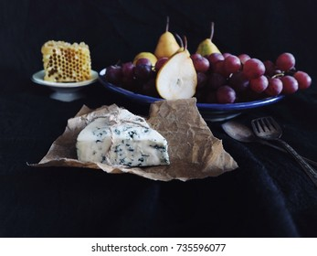 Blue cheese/Roquefort cheese with fresh pears, grapes and honeycomb. Vintage silver spoons, black fabric, dark background. Vintage plate.  Fruits, cheese, side view. Delicacy food. Snack/appetizer