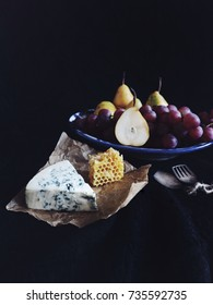 Blue cheese/Roquefort with fresh pears, grapes and honeycomb. Vintage silver spoons, black fabric. Fruits, cheese, side view. Delicacy food. Snack/appetizer