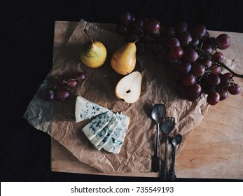 Blue cheese/Roquefort plate with fresh pears, grapes. Vintage silver spoons, black fabric. Fruits, cheese, top view. Delicacy food. Snack/appetizer