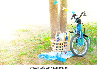 Blue Children Bicycle Decorated with Colorful Flags Stands near Tree. Bithday Holiday Outdoors Picnic with Presents Basket. Bithday Concept