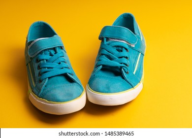 Blue children's gym shoes with a white sole on a flypaper on a yellow background