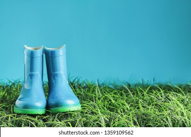 Blue children's rain boots / wellies sitting in the grasss agaisnt a blue background with room for copy space.