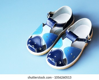 Blue child's sandals on blue background, object