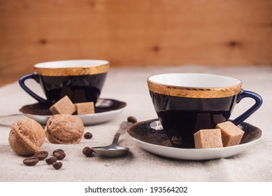 Blue china cup with brown sugar, cookies, and muffins on table